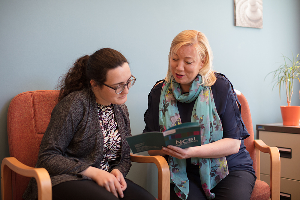 NCBI staff member giving information to service user