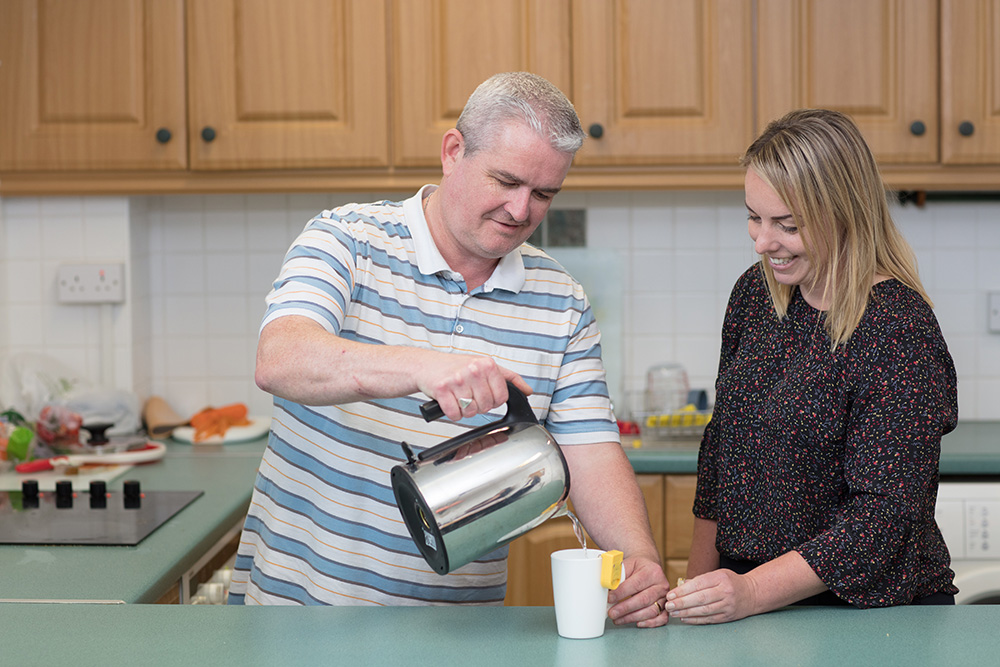 Service user pouring hot water into a cup in the kitchen with Chantelle helping