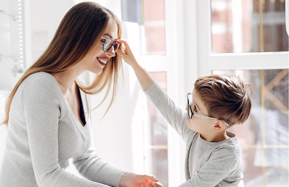 young boy pulling glasses of his mother.