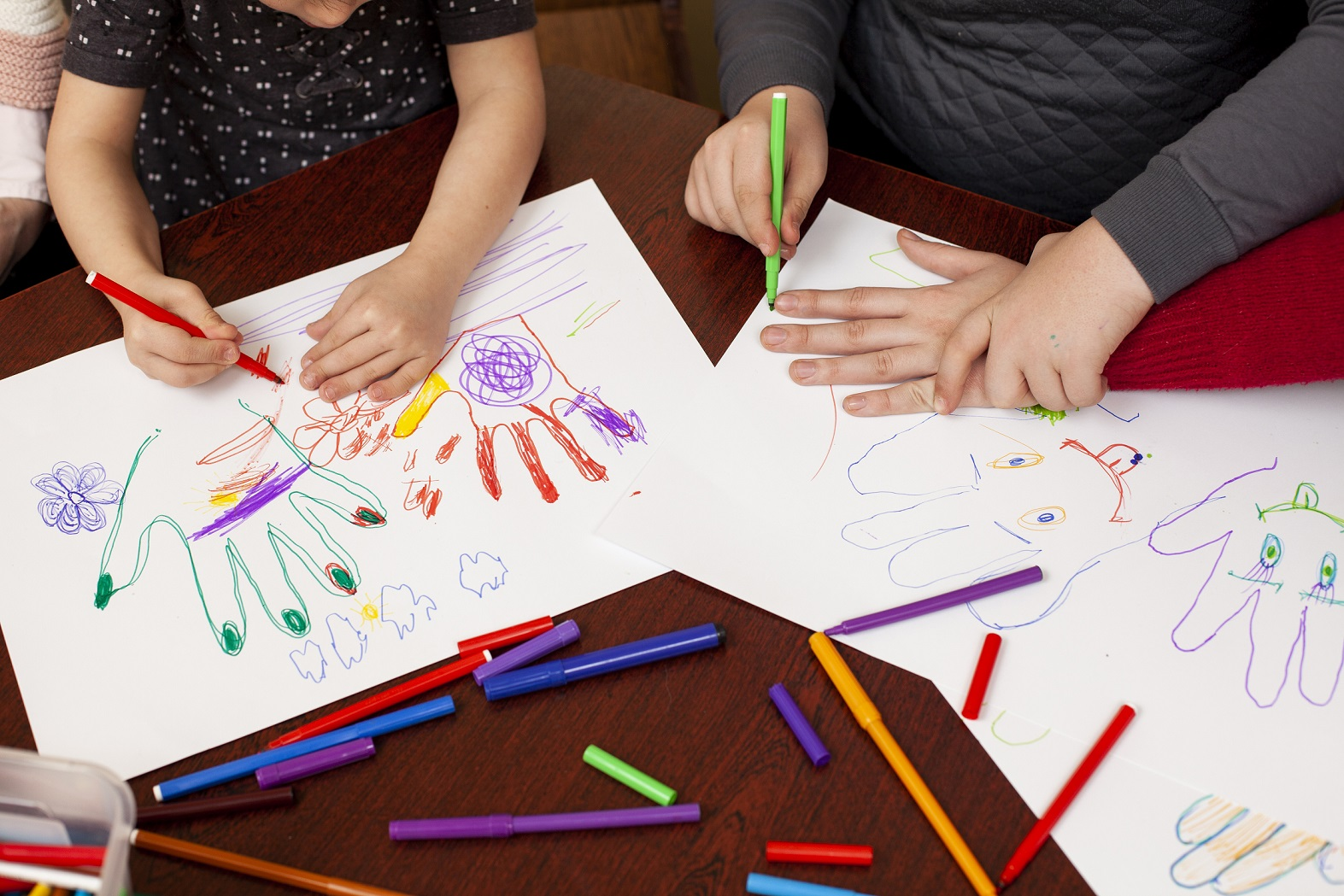 children drawing using coloured pencils