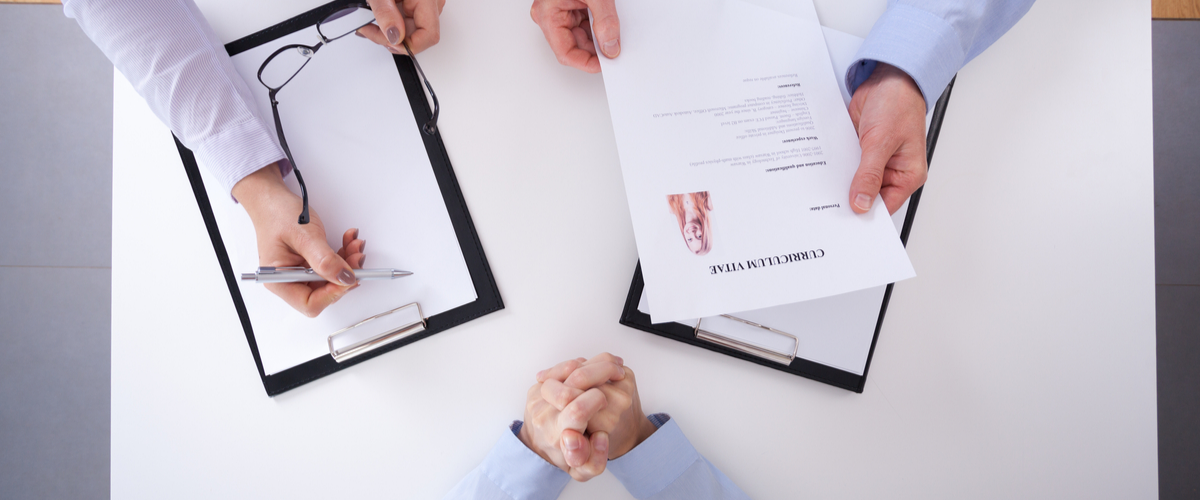 Image of employer holding a CV.