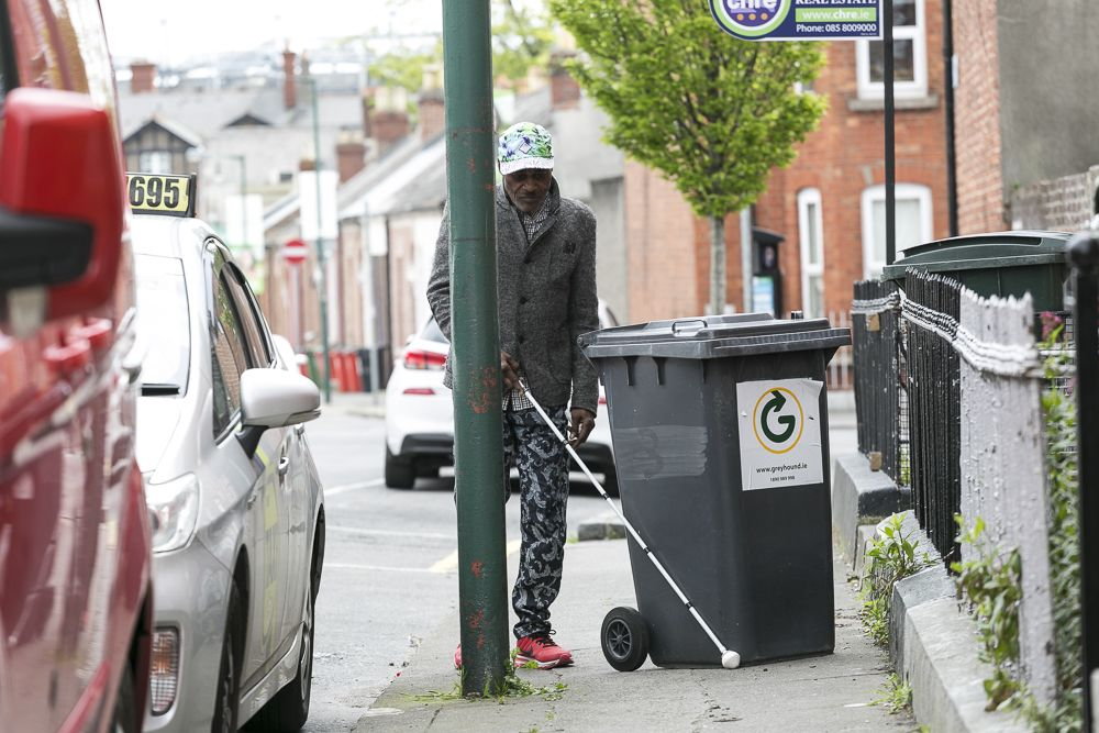 Man walking with a white cane, black bin in his way