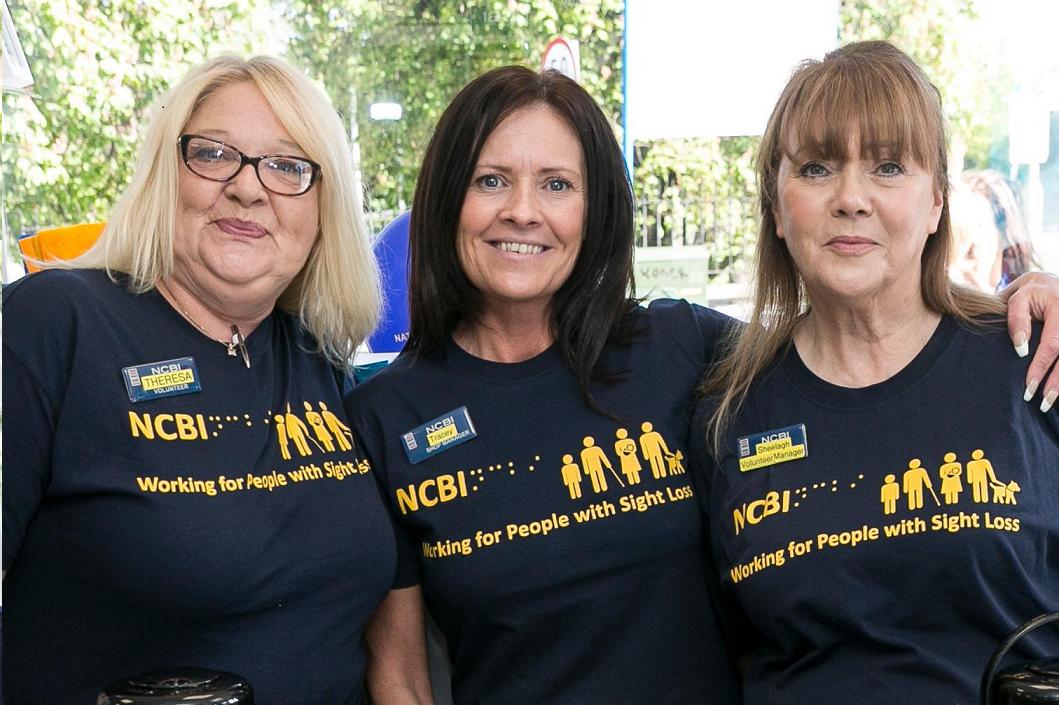 Photo of three middle age women wearing a dark blue NCBI t-shirt
