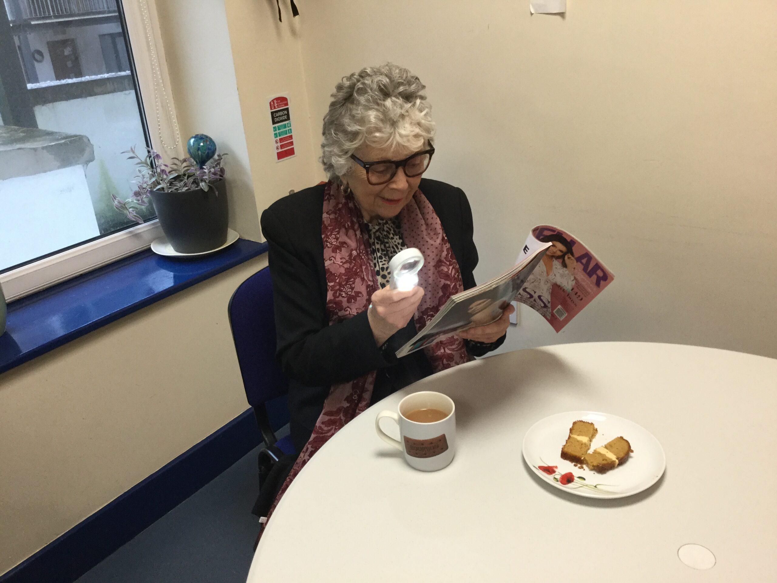 Image of Margaret reading using magnifier