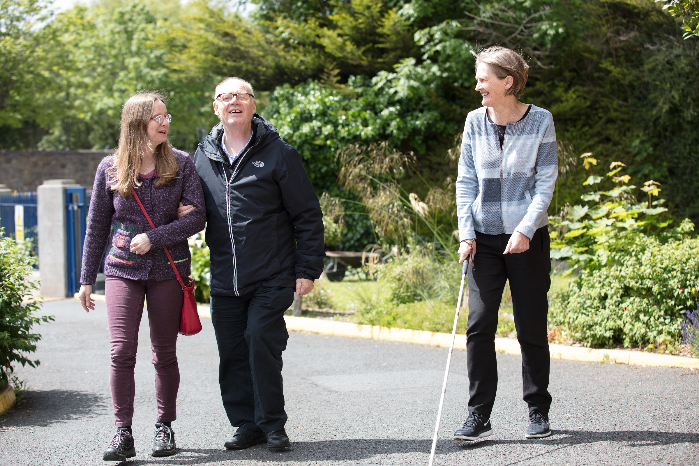 3 service users walking, one with a white cane