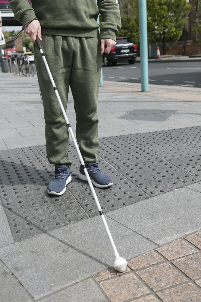 Image of cane user on tactile pavement