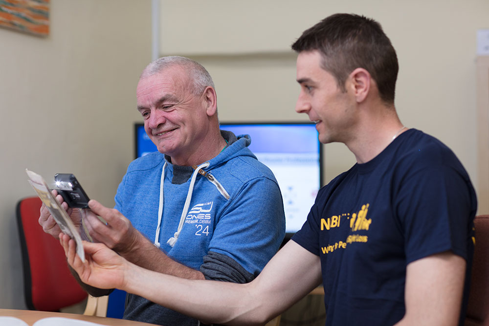 staff member showing a service user assistive technology
