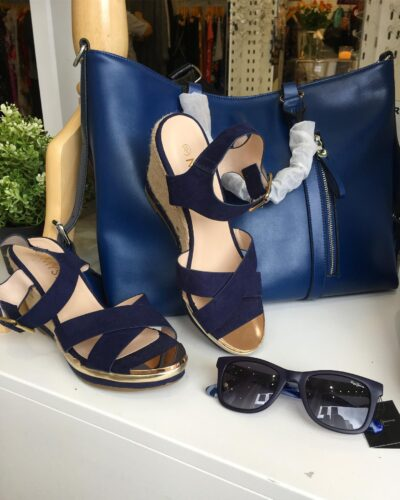 a paif of dark blue high shoes and a beautiful blue letter purse and a sungless