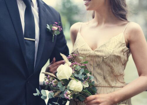 Photo of a couple, the women is holding a bouquet and the man is wearing a suit