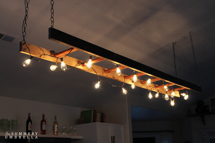 A ladder hanging from a ceiling with large bulbs wrapped around it
