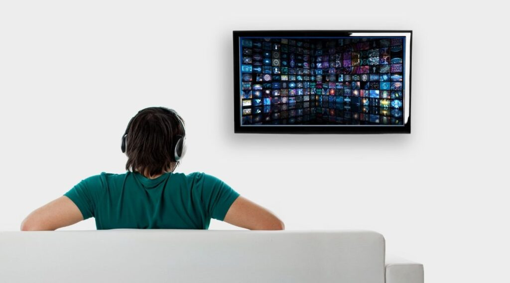 A man watching TV with his headphones