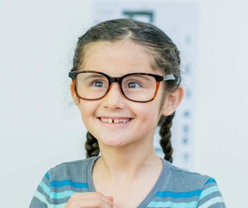 girl ooking excited aged about 10, wearing a pair of glasses, with braided and a blue top on